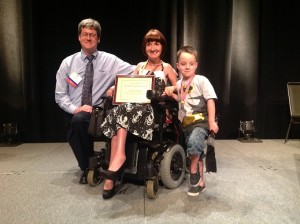 Lisa Lehmann, Words+/ ISAAC Outstanding Consumer Lecture Award winner, with son Hunter and Jeff Dahlen of Words+, Inc.